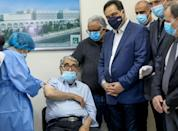 Lebanon's caretaker premier Hassan Diab (4th R) poses for a picture while actor Salah Tizani, 93, receives a first dose of the Pfizer/BioNTech vaccine in the capital Beirut