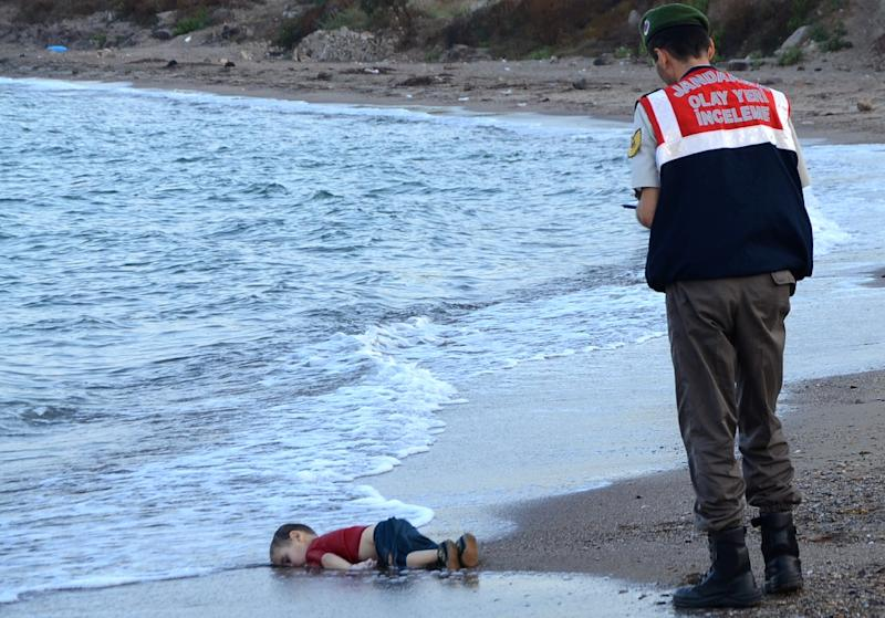 A Turkish police officer stands next to the body of Aylan Kurdi in September 2015