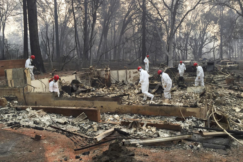 FILE - In this Nov. 15, 2018 file photo, volunteer rescue workers search for human remains in the rubble of homes burned in the Camp Fire in Paradise, Calif. Northern California officials have struggled to get a handle on the number of missing from the deadliest wildfire in at least a century in the United States. Authorities continue to log hundreds of reports by people who couldn't reach loved ones in the aftermath of the Camp Fire in Butte County. (AP Photo/Terry Chea, File)