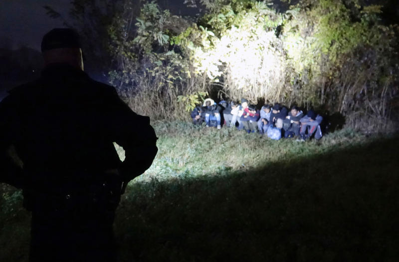 In this photo taken Saturday, Nov. 9, 2019, Bosnian border police officers guard migrants after making the illegal crossing from Serbia by the Drina river, the natural border between Bosnia and Serbia, near eastern Bosnian town of Zvornik, Bosnia. Bosnian border police are warning they cannot contain migratory pressures along the country's eastern border with Serbia, warning the situation could easily escalate and put in danger the overall stability of their politically fragile nation. (AP Photo/Eldar Emric)