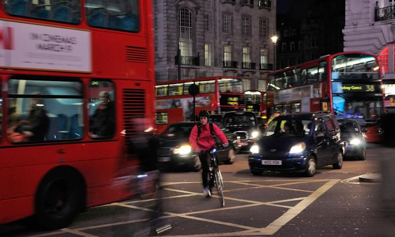 Cyclists negotiating London traffic at night