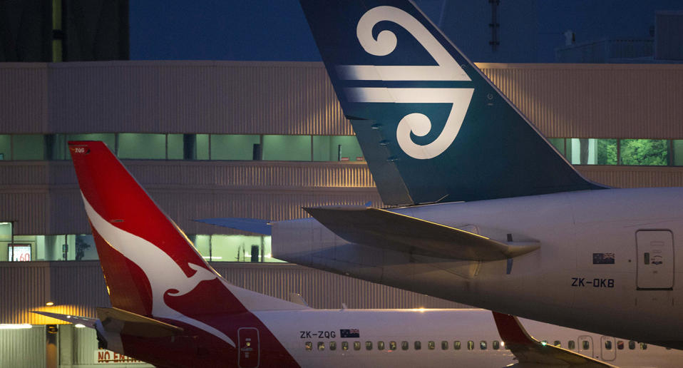 The tails of a Qantas plane and an Air New Zealand plane are seen parked at a gate.