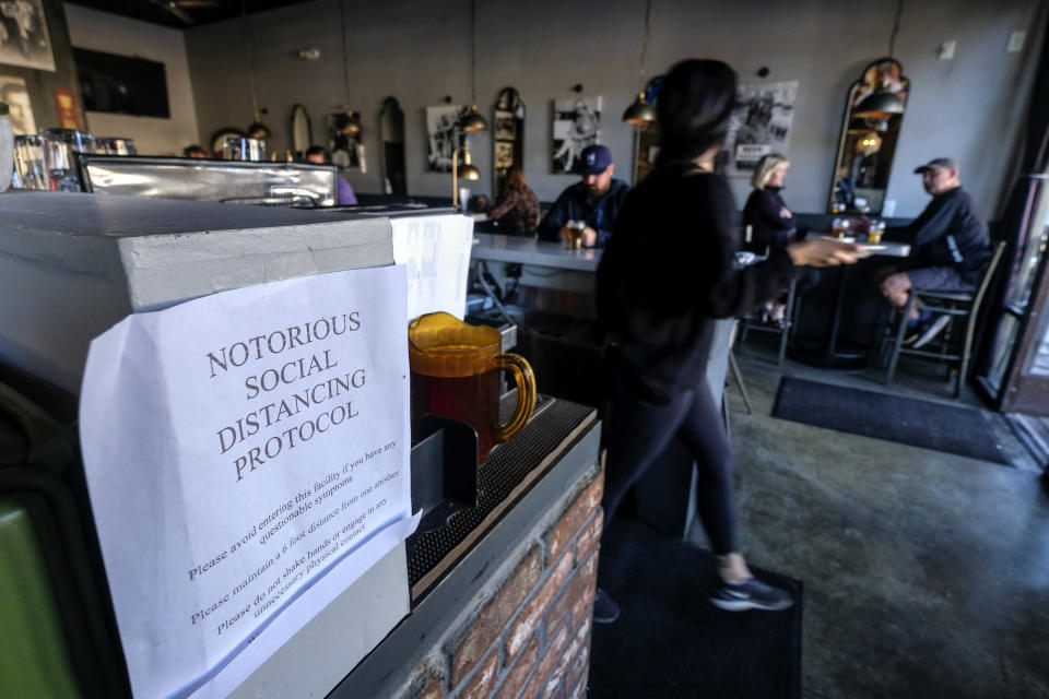A notice, that reminds patrons to observe social distancing measures, is displayed at Notorious Burgers restaurant in Carlsbad, Calif., on Friday, Dec. 18, 2020. (AP Photo/Ringo H.W. Chiu)