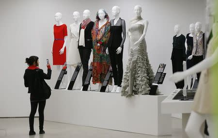 "A visitor takes a photo of a display of dresses in the ""Women Fashion Power exhibition at the Design Museum in London November 4, 2014. REUTERS/Suzanne Plunkett"