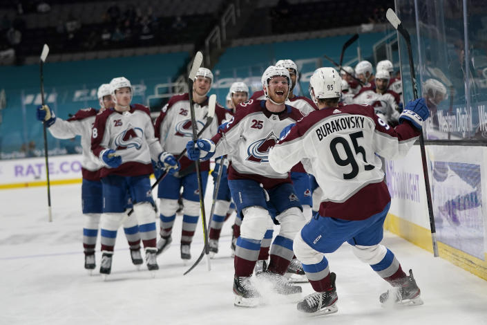 Colorado Avalanche left wing Andre Burakovsky (95) celebrates with teammates after scoring during overtime of an NHL hockey game against the San Jose Sharks in San Jose, Calif., Monday, May 3, 2021. The Avalanche won, 5-4. (AP Photo/Jeff Chiu)