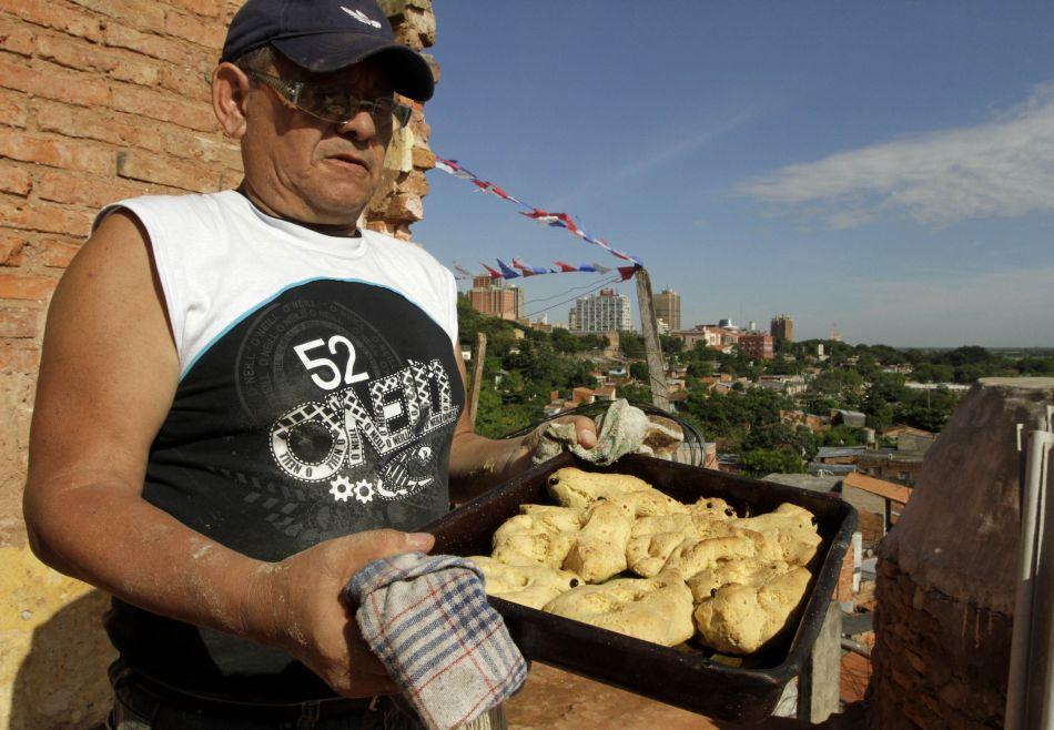 Paraguayan Clemente Caceres prepares chipas, a typical bread made from corn flour, eggs, milk and lard, that he bakes in a clay oven called a tatakua to be eaten especially during Easter Week celebrations when Catholics avoid meat, on the outskirts of Asuncion.