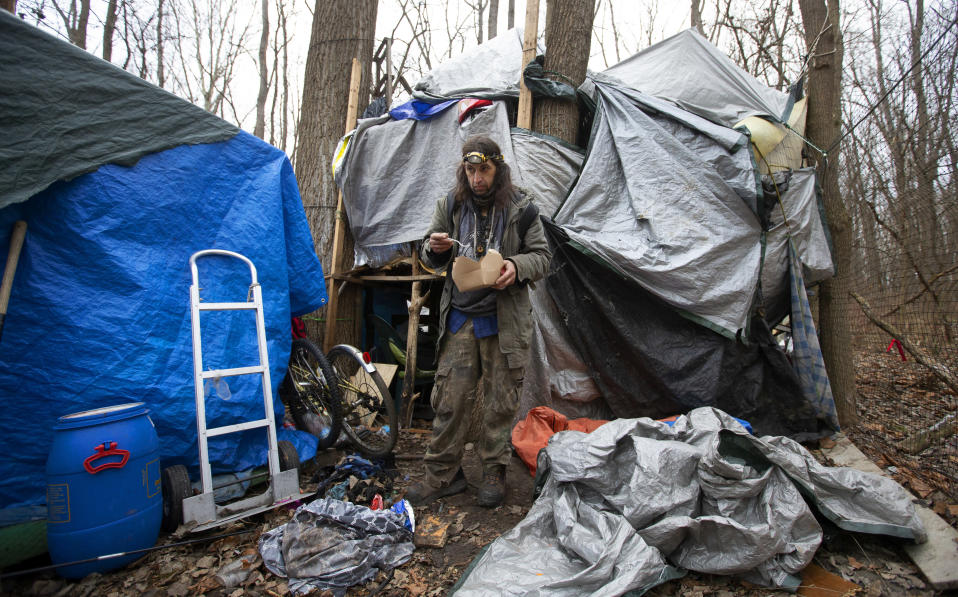 """Jose Ortiz eats a boxed meal delivered by volunteers to the residence he built in the homeless encampment known as the Jungle on Monday, Dec. 7, 2020, in Ithaca, N.Y. When Jose Ortiz tested positive for COVID-19 last month, he was able to isolate at his elaborately crafted shelter, which includes a """"treehouse"""" about waist-high with a wood stove pipe and a tree protruding from the tarp-covered top. (AP Photo/John Munson)"""