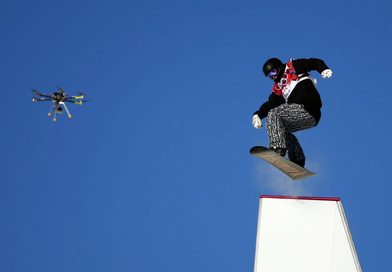 Finland's Janne Korpi performs a jump as a drone is seen in the air during the men's snowboard slopestyle semi-final competition at the 2014 Sochi Olympic Games in Rosa Khutor