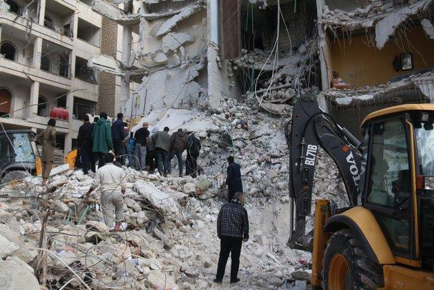 Syrian civil defense members conduct search and rescue operations at the site of the blast that leveled a seven-story building in Idlib, which Lord Richards has said the West should intervene to protect