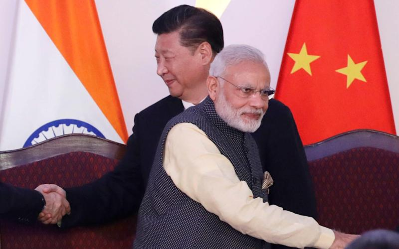 In this Oct. 16, 2016, file photo, Indian Prime Minister Narendra Modi, front and Chinese President Xi Jinping shake hands with leaders at the BRICS summit in Goa, India
