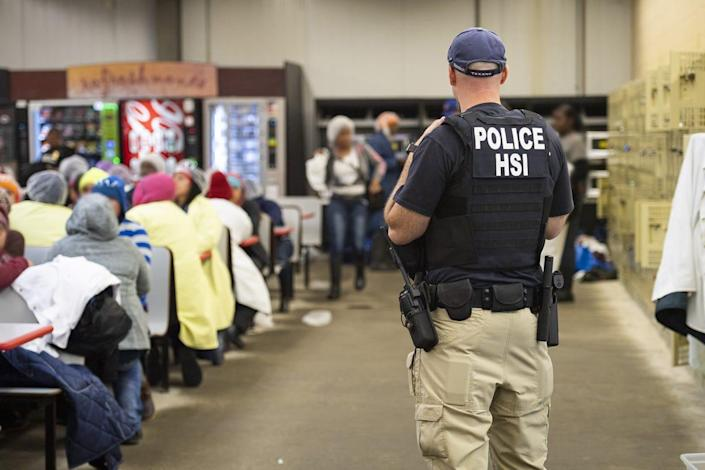 """This image released by the US Immigration and Customs Enforcement (ICE) shows a Homeland Security Investigations (HSI) officer guarding suspected illegal aliens on August 7, 2019. Officers detained approximately 680 aliens who were unlawfully working at at seven agricultural processing plants across Mississippi. - US officials said that some 680 undocumented migrants were detained in a major series of raids on August 7, at food processing plants in the southeastern state of Mississippi, part of President Donald Trump's announced crackdown on illegal immigration. """"Special agents executed administrative and criminal search warrants resulting in the detention of approximately 680 illegal aliens,"""" said Mike Hurst, US Attorney for the Southern District of Mississippi. (Photo by HO / US Immigration and Customs Enforcement / AFP)"""