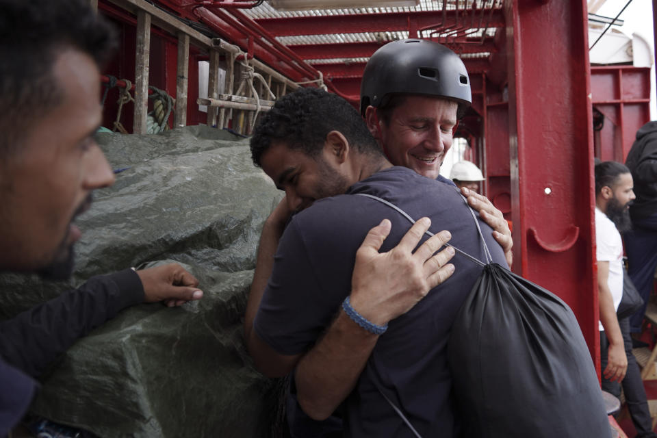 A migrant hugs an SOS Mediterranee rescuer aboard the Ocean Viking ship before stepping into the port of Messina, Italy, Tuesday, Sept. 24, 2019. He was among 182 people aboard the Ocean Viking rescued in the Mediterranean Sea north of Libya. (AP Photo/Renata Brito)