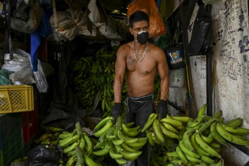 A man wears a face mask as he works at a market in Medellin, Colombia, on March 19, 2020