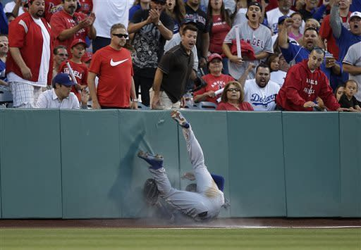 Los Angeles Dodgers' Carl Crawford, center, tumbles after catching a ball hit by Los Angeles Angels' Alberto Callaspo during the second inning of an interleague baseball game in Anaheim, Calif., Thursday, May 30, 2013. (AP Photo/Jae C. Hong)