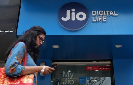 A woman checks her mobile phone as she walks past a mobile store of Reliance Industries' Jio telecoms unit in Mumbai