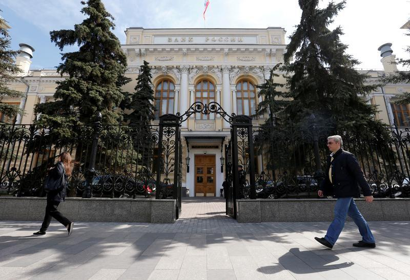 People walk past the Central Bank headquarters in Moscow