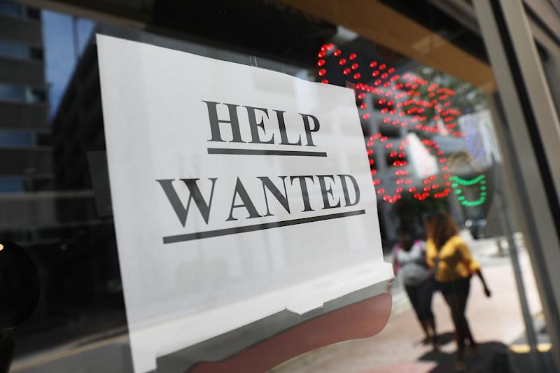 "A ""help wanted"" sign hangs on a window of a restaurant in Miami, Florida. Image Source: Getty"