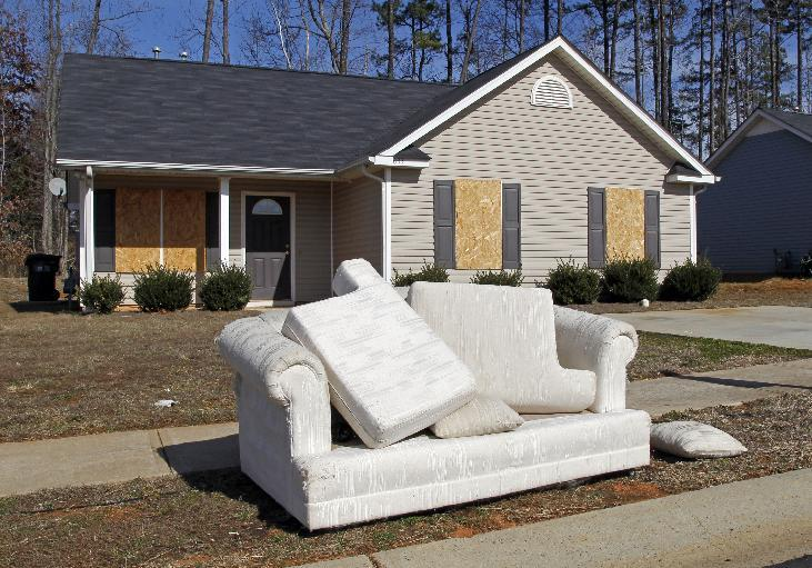 """FILE - This Tuesday, Feb. 15, 2011 file photo shows a discarded sofa in front of an abandoned house in the Windy Ridge subdivision of Charlotte, N.C. In 2008, Obama became the first Democrat to take North Carolina since Jimmy Carter in 1976. Pundits called the victory historic, but it came by the slimmest of margins _ just 14,000 votes out of nearly 4.4 million cast. History suggests that if the economy doesn't show substantial improvement in the year before a presidential election, the incumbent loses. And North Carolina's recovery from the """"Great Recession"""" has lagged behind the nation's. (AP Photo/Bob Leverone, File)"""