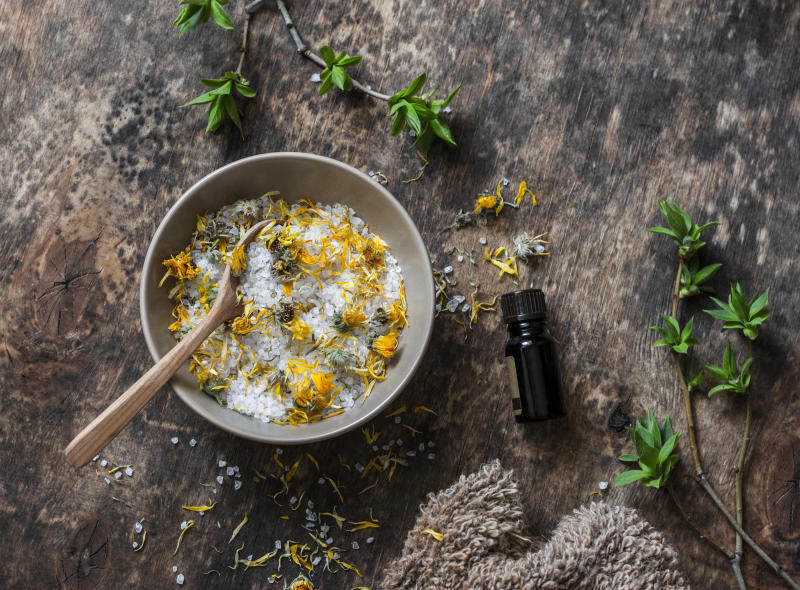 Homemade calendula, essential oil dead sea salt on wooden background, top view