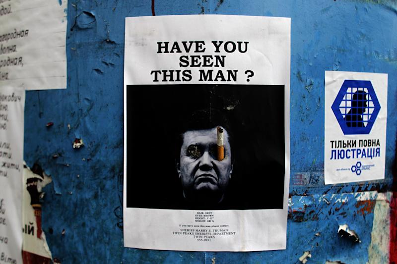 A poster with a photo of fugitive Ukrainian President Viktor Yanukovych, who fled the capital Kiev and went into hiding after months of protests against his government, is seen fixed onto a barricade in central Kiev, Ukraine, Thursday, Feb. 27, 2014. Ukraine put its police on high alert after dozens of armed pro-Russia men stormed and seized local government buildings in Ukraine's Crimea region early Thursday and raised a Russian flag over a barricade. (AP Photo/Marko Drobnjakovic)