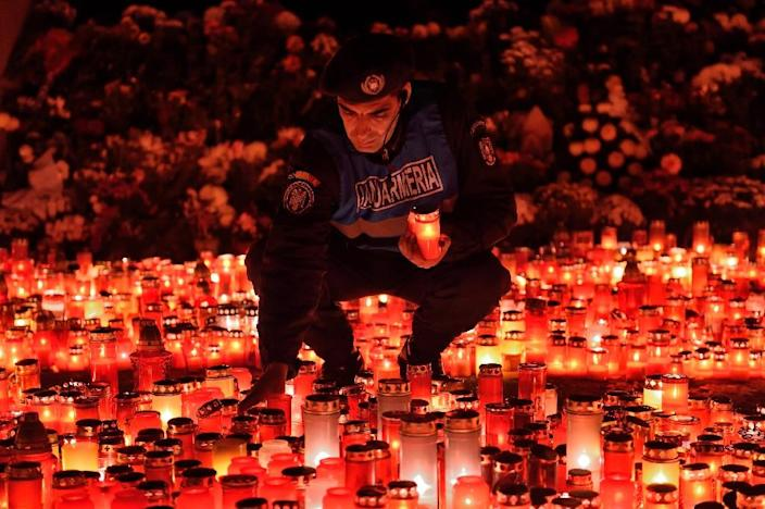 """A Romanian gendarme places candles at a memorial for the victims of the fire at the """"Colectiv"""" nightclub in Bucharest on November 2, 2015 (AFP Photo/Daniel Mihailescu)"""