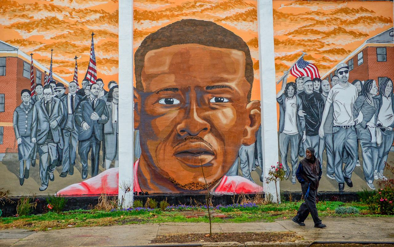 A man, who declined to offer his name, walks past a mural of Freddie Gray in the Sandtown-Winchester neighborhood of Baltimore, December 17, 2015.  On Wednesday, Judge Barry Williams declared a mistrial in the case of Police Officer William Porter, one of six officer charged connection with the death of Freddie Gray.  REUTERS/Bryan Woolston        EDITORIAL USE ONLY. NO RESALES. NO ARCHIVE