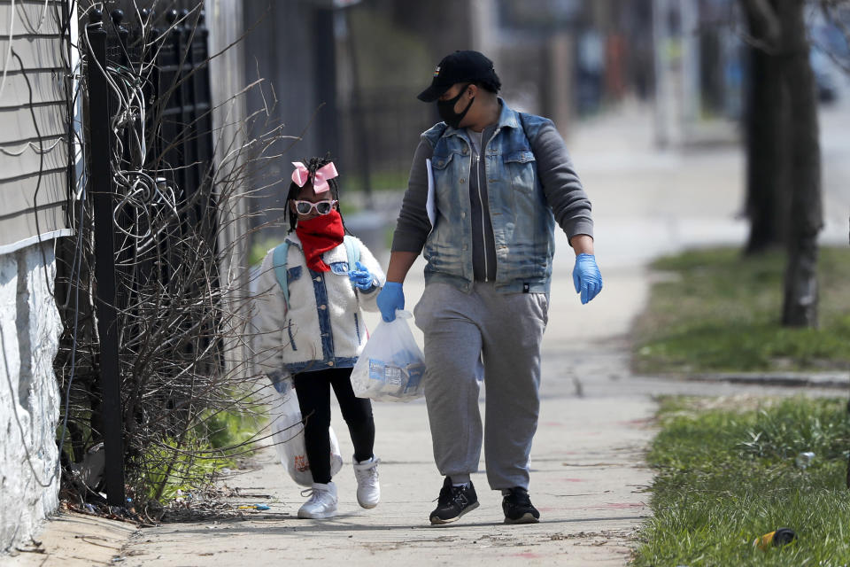 In this April 7, 2020, photo, Erica Harris, right, and her daughter Jordan, wear their protective masks as they walk back home after getting a lunch and homework from the child's school on Chicago's Southside in Chicago. As the coronavirus tightened its grip across the country, it is cutting a particularly devastating swath through an already vulnerable population, black Americans. (AP Photo/Charles Rex Arbogast)