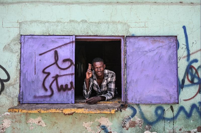 A Sudanese vendor flashes the V for victory sign during a protest near the army hearquarters in the capital Khartoum on Sunday (AFP Photo/OZAN KOSE)