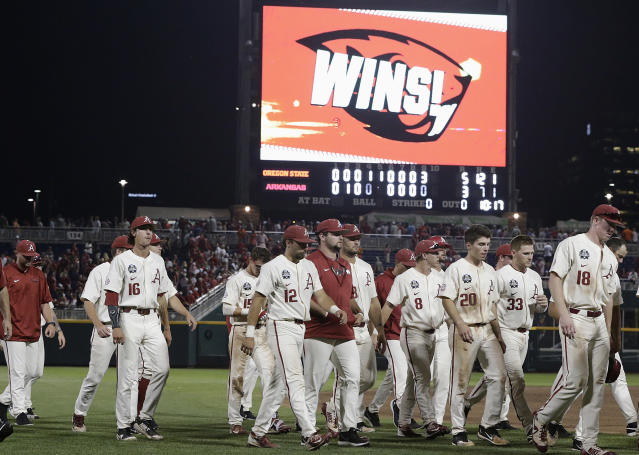 Arkansas players walk off the field after losing to Oregon State in Game 2 of the NCAA College World Series baseball finals in Omaha, Neb., Wednesday, June 27, 2018. (AP Photo/Nati Harnik)