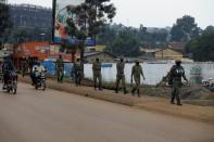 Ugandan security forces walk in a formation in Kampala