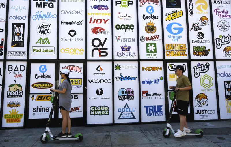 This Wednesday, Aug. 28, 2019, photo shows advertising logos for different cannabis brands posted on the side of a shop on a street lined with wholesale cannabis vape shops in downtown Los Angeles. A short walk from police headquarters in the heart of downtown, a cluster of bustling shops are openly selling packaging and hardware that can be used to produce counterfeit, and potentially dangerous, marijuana vapes that have infected California's cannabis market and possibly sickened dozens of people. (AP Photo/Richard Vogel)