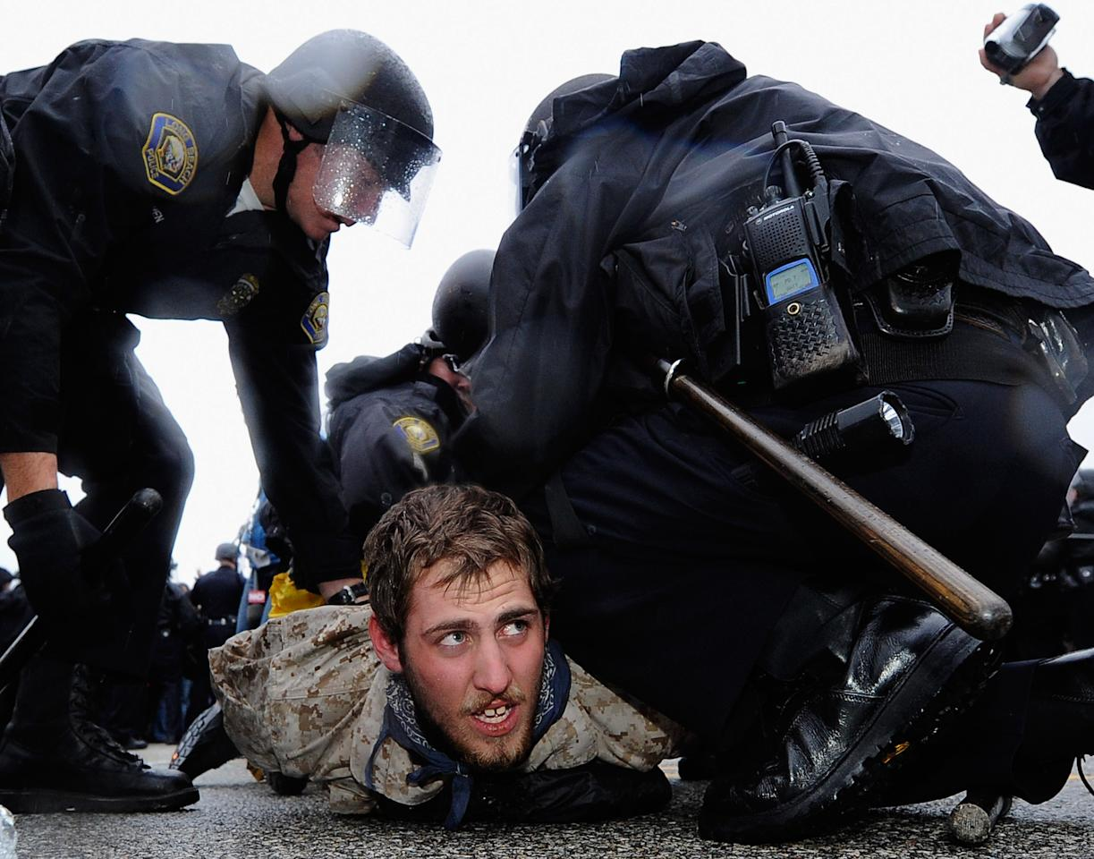 LONG BEACH, CA - DECEMBER 12:  A man is arrested by Long Beach Police Department officers after protestors blocked the road leading to SSA Marine, a shipping company that is partially owned by investment bank Goldman Sachs at the Port of Long Beach on December 12, 2011 in Long Beach, California. Following a general strike coordinated by Occupy Oakland that closed the Oakland port on November 2 hundreds are expected to try and shut down all West Coast ports as Occupy movements in Los Angeles, San Diego, Oakland, Portland, Seattle and Tacoma have joined the demonstration.  (Photo by Kevork Djansezian/Getty Images)