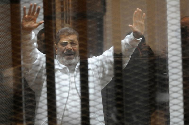 Egypt's deposed Islamist president Mohamed Morsi waves from inside the defendant's cage during his trial at the police academy in Cairo on January 8, 2015 (AFP Photo/STR)