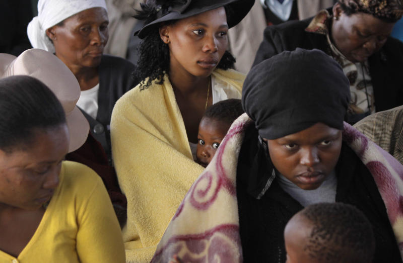Mourners attend a memorial service at the Lonmin Platinum Mine near Rustenburg, South Africa, Thursday, Aug. 23, 2012 after police shot and killed 34 striking miners and wounded 78 last week. Demands for higher wages spread to at least two other mines, raising fears of further protests at more South African mines that provide most of the world's platinum.  (AP Photo/Denis Farrell)