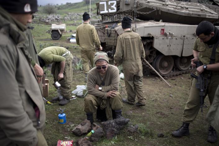Israeli soldiers take a break at their position near the border with Syria in the Israeli-controlled Golan Heights, Wednesday, Feb. 26, 2014. Hezbollah says Israel carried out an airstrike targeting its positions in Lebanon near the border with Syria earlier this week, claiming it caused damage but no casualties. The Wednesday statement was the group's first acknowledgement of the reported Monday night airstrikes. (AP Photo/Ariel Schalit)