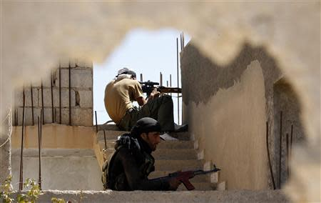 Free Syrian Army fighters get into shooting positions in the suburbs of Raqqa