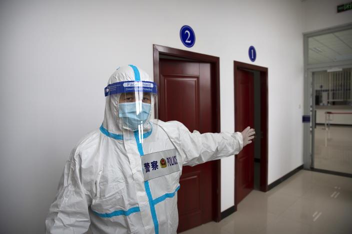 A security officer in a protective suit gestures as he stands in a hallway with rooms for video meetings with inmates at the visitors' hall at the Urumqi No. 3 Detention Center in Dabancheng in western China's Xinjiang Uyghur Autonomous Region on April 23, 2021. (AP Photo/Mark Schiefelbein)