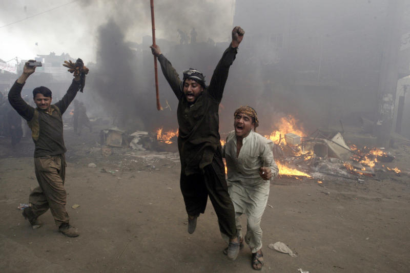 Pakistani men, part of an angry mob, react after burning belongings of Christian families, in Lahore, Pakistan, Saturday, March 9, 2013. A mob of hundreds of people in the eastern Pakistani city of Lahore attacked a Christian neighborhood Saturday and set fire to homes after hearing accusations that a Christian man had committed blasphemy against Islam's prophet, said a police officer. (AP Photo/K.M. Chaudary)