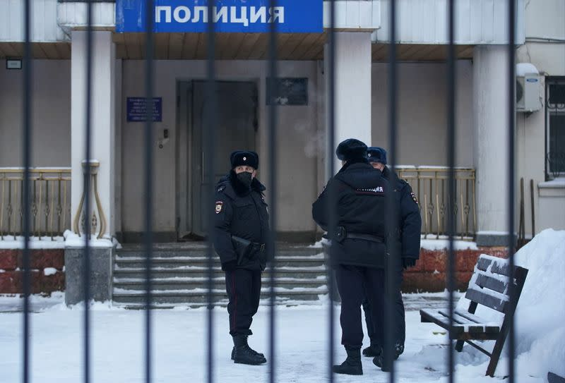 Police officers stand outside a police station where detained Russian opposition leader Navalny is being held, in Khimki