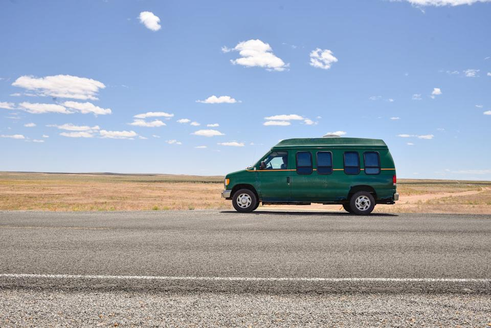 A green van is seen on a sunny, deserted highway.