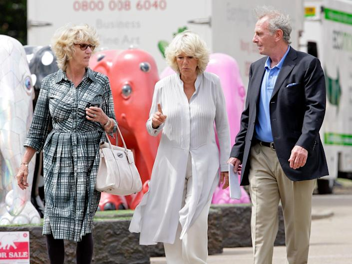 Camilla, Duchess of Cornwall walks between her sister Annabel and brother Mark.