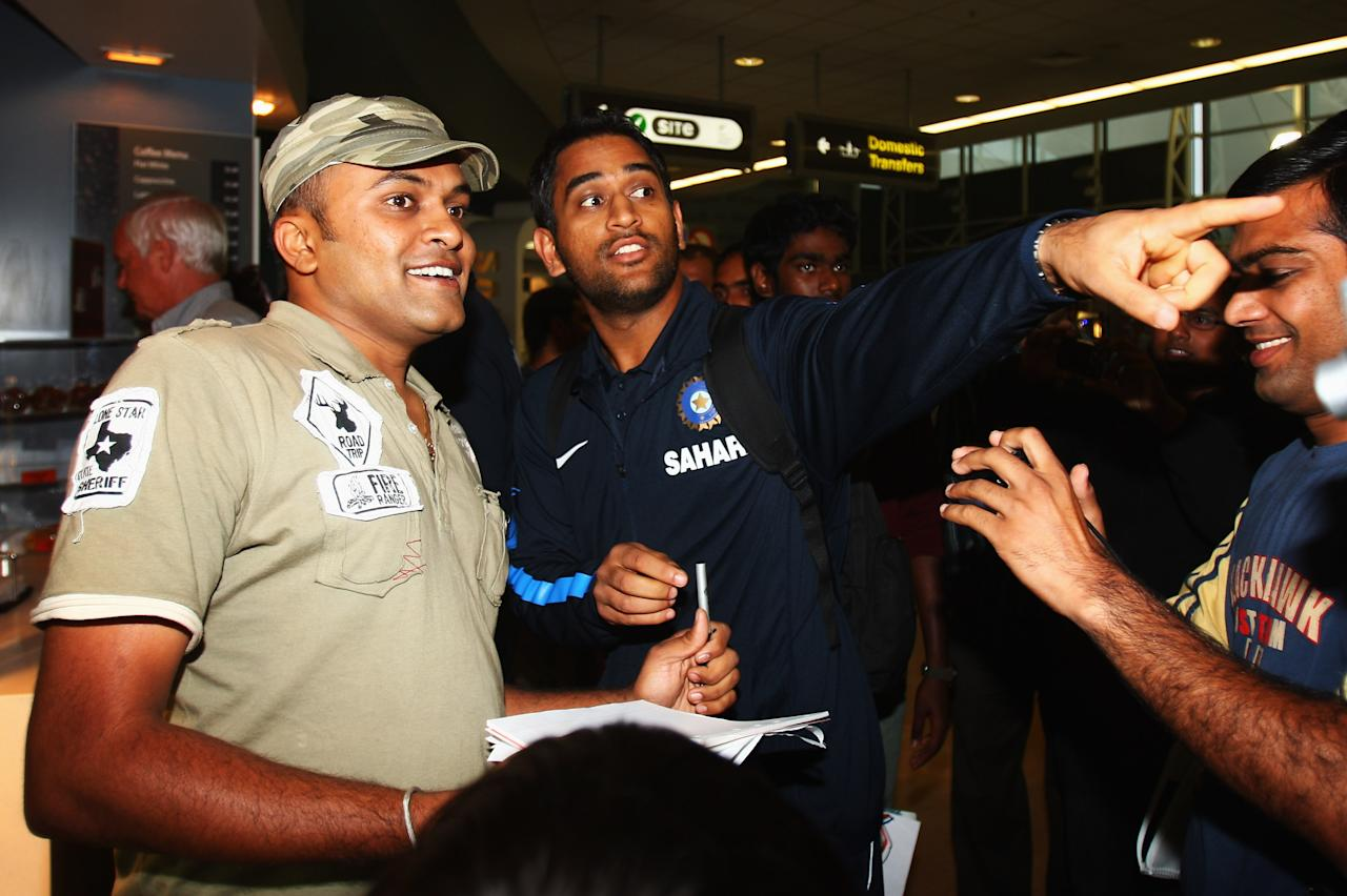 AUCKLAND, NEW ZEALAND - FEBRUARY 20:  MS Dhoni of India points out Sachin Tendulkar to deter the fans at the arrivals hall as the Indian cricket team arrive at Auckland International Airport on February 20, 2009 in Auckland, New Zealand. The Indian will play New Zealand in two Twenty20 International, five One Day Internationals and three Test matches during their tour.  (Photo by Sandra Mu/Getty Images)