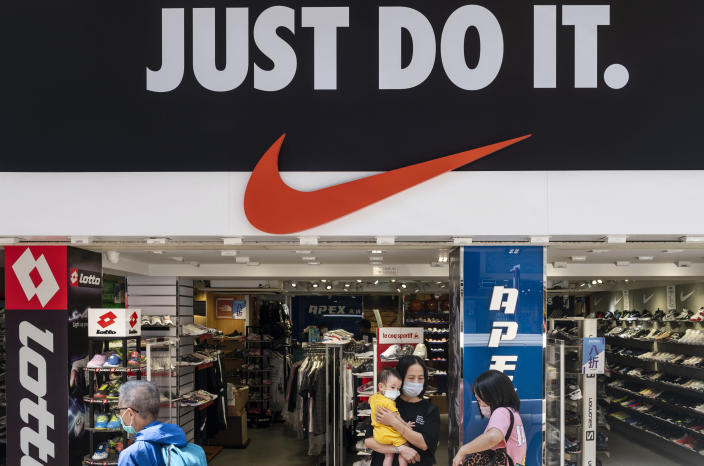 """HONG KONG, CHINA - 2020/08/28: Pedestrians wearing masks walk past American multinational sport clothing brand Nike store, logo, with a slogan """"Just Do It"""" in Hong Kong. (Photo by Budrul Chukrut/SOPA Images/LightRocket via Getty Images)"""