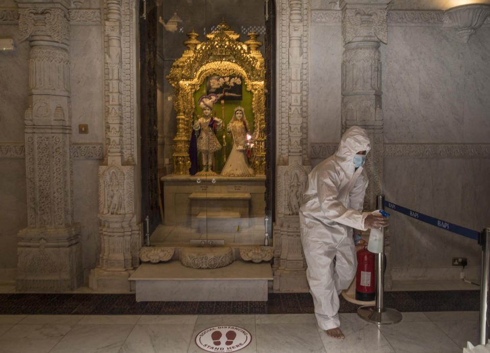 After each prayer session, workers in full-body protective suits sanitize any surface that may have been touched at the BAPS Shri Swaminarayan Mandir, also known as the Neasden Temple, in London on Friday, July 3, 2020. The magnificent temple of carved stone constructed according to ancient Vedic architectural texts usually welcomes thousands of visitors a day but now gets just a trickle of devotees who book appointments online first to keep the crowds down. (AP Photo/Elizabeth Dalziel)