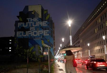 """Woman walks along a street in the early morning near a lettering reading """"The Future is Europe"""" near the European Council headquarters ahead of an EU summit in Brussels"""