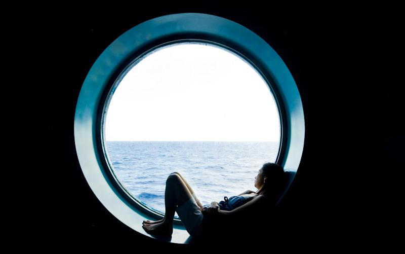 Girl daydreaming at a porthole - Getty