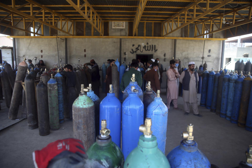People line up for free oxygen at a privately owned oxygen factory, in Kabul, Afghanistan, Thursday June 18, 2020. For seven years, Najibullah Seddiqi's oxygen factory sat idle in the Afghan capital Kabul. He shut it down, he says, because corruption and power cuts made it impossible to work. But when the novel coronavirus began racing through his country, he opened the factory's dusty gates and went back to work. Now he refills hundreds of oxygen cylinders a day for free for COVID-19 patients — and at reduced rates for hospitals. (AP Photo/Rahmat Gul)
