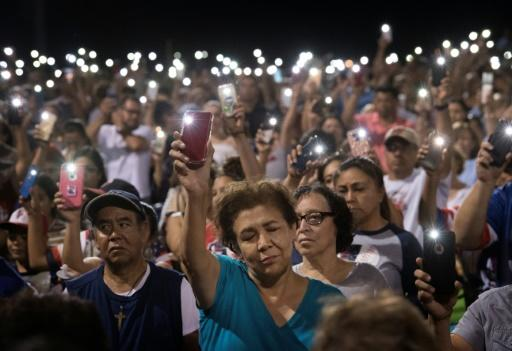 People hold up their phones during a prayer and candlelight vigil after a shooting left 22 people dead in El Paso, Texas