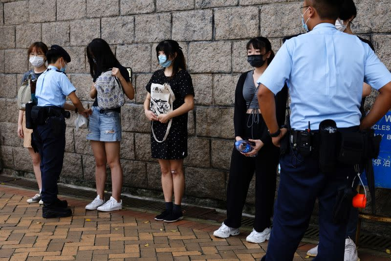 Police stop and search supporters of Tong Ying-kit, the first person charged under a new national security law, during court hearing outside the High Court, in Hong Kong