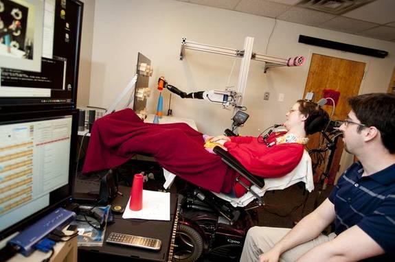 Scheuermann stacks cones with a mind-controlled robot arm. Research assistant Brian Wodlinger, Ph.D., watches her work.